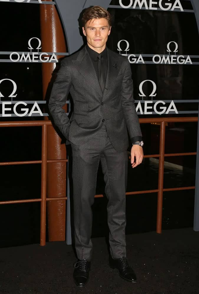 Oliver Cheshire dressed in a monochrome suit at an Omega event
