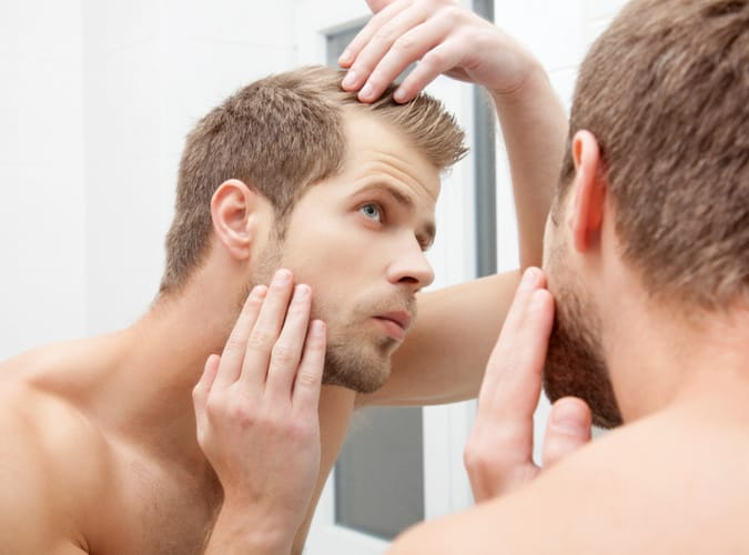 Man Checking His Hairline In The Mirror