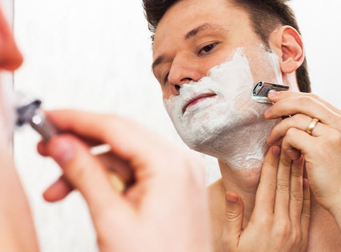 Man Shaving With A Double Edge Razors