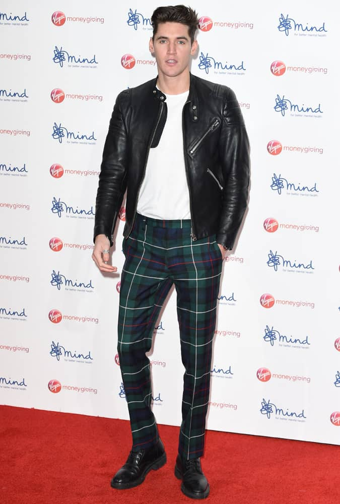 Isaac Carew wearing check trousers and a leather biker jacket