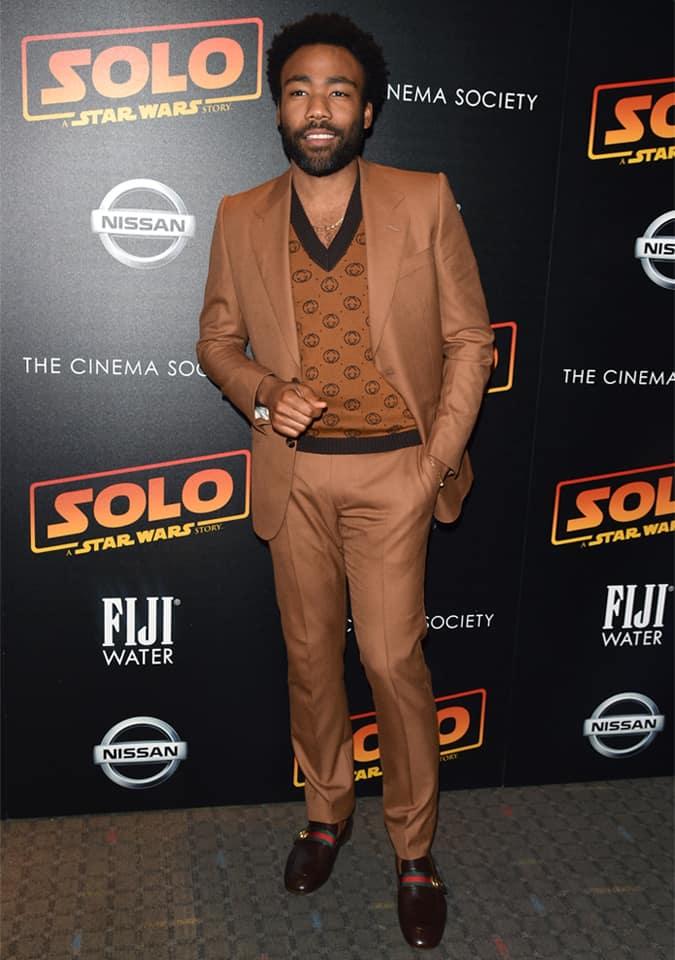 Donald Glover en costume marron